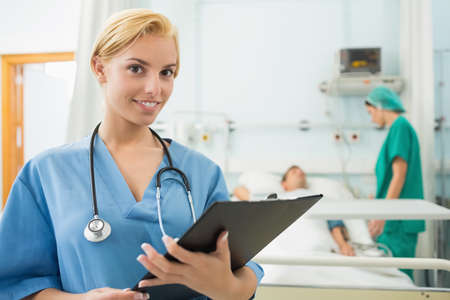 keep watch over: Blonde nurse holding a chart while looking at camera in hospital ward