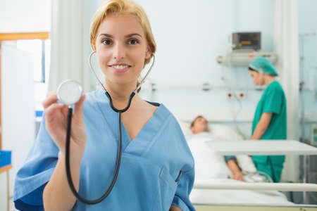 keep watch over: Blonde nurse holding a stethoscope in hospital ward