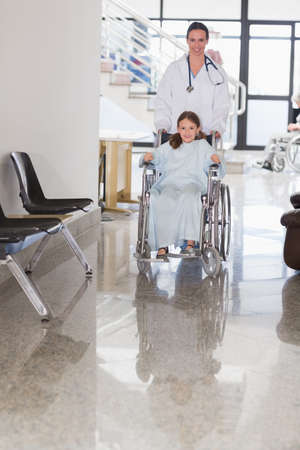 wheeling: Smiling doctor wheeling a smiling girl in a wheelchair in a hospital