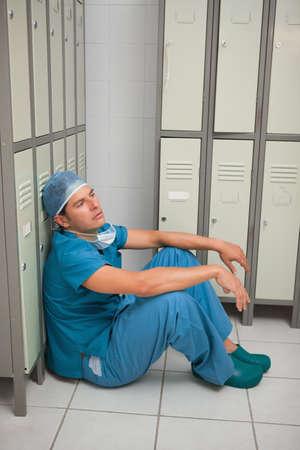 weaken: Surgeon sitting in a locker room of a hospital LANG_EVOIMAGES