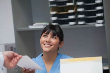 nurse station: Smiling nurse behind a desk giving a file to a doctor in a hospital