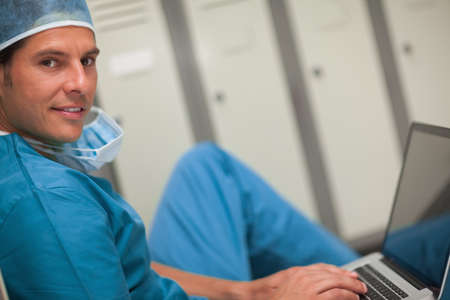 locker room: Surgeon using a laptop while sitting on a locker room in a hospital