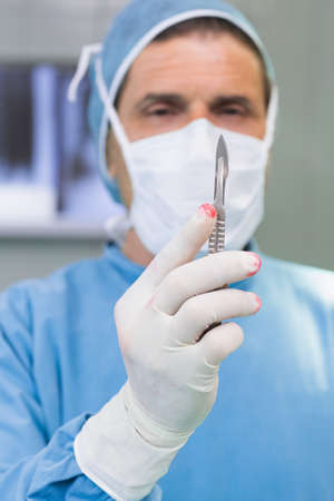earnest: Surgeon holding a scalpel in his gloved hand in an operating theater LANG_EVOIMAGES