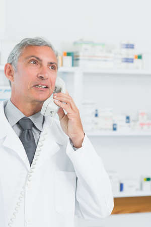 telephoning: Pharmacist standing in a pharmacy while telephoning in a hospital LANG_EVOIMAGES