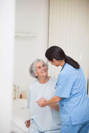 keep watch over: Nurse helping a smiling senior patient in a hospital bedroom