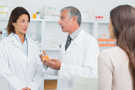 earnest: Pharmacist talking to a colleague in front of a patient in a pharmacy