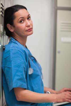 desolaci�n: Cirujano de sexo femenino que se sienta en un vestuario con un ordenador port�til en un hospital