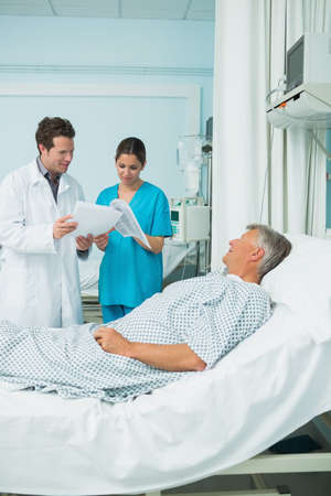 keep watch over: Patient lying on a bed while looking at a doctor and a nurse in a hospital