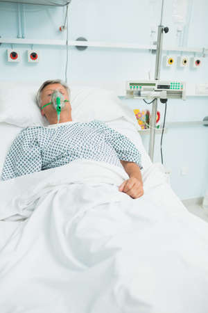 conscious: Conscious senior male patient lying on a bed with an oxygen mask in a hospital