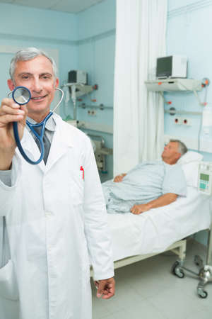 recuperation: Smiling doctor with his stethoscope in a hospital ward