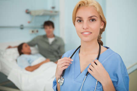keep watch over: Blonde nurse looking at camera next to a patient in hospital ward LANG_EVOIMAGES