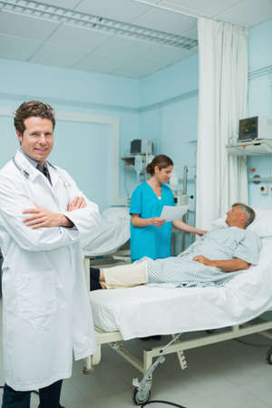 keep watch over: Smiling male doctor with his arms folded in the foreground of a hospital room