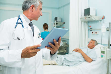 recuperation: Doctor using a tactile tablet while looking at a patient in a hospital bed ward LANG_EVOIMAGES