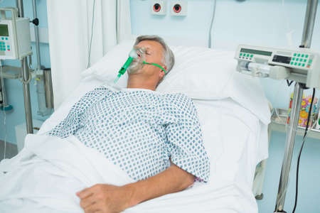 the unconscious: Unconscious patient on a bed with an oxygen mask in a hospital
