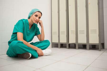 locker room: Nurse sitting crosslegged on the floor in locker room