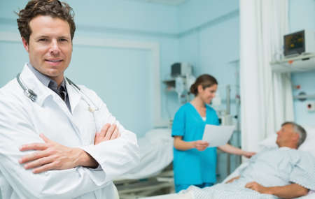 keep watch over: Male doctor with his arms folded in the foreground of a hospital room LANG_EVOIMAGES
