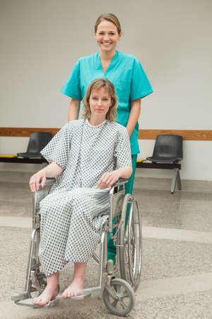 paraplegic: Smiling nurse wheeling a female patient in a corridor