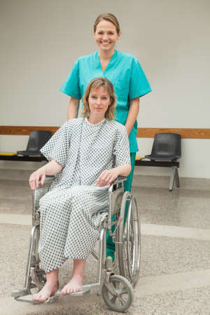 wheeling: Smiling nurse wheeling a female patient in a corridor