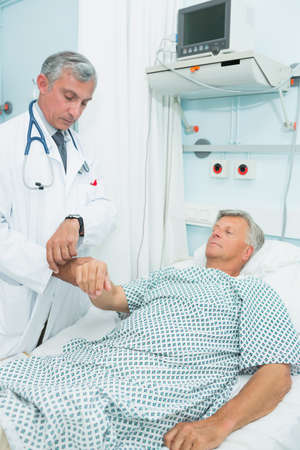 recuperation: Doctor measuring the pulse of a male patient in a hospital