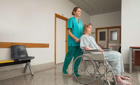 wheeling: Nurse wheeling the wheelchair of a female patient in a corridor