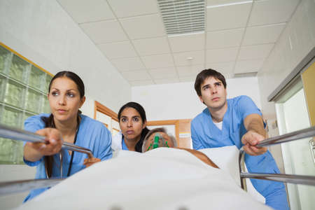 wheeling: Medical team wheeling the bed of a patient in a hospital hallway LANG_EVOIMAGES