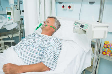 recuperation: Unconscious patient lying on a bed with an oxygen mask on in a hospital LANG_EVOIMAGES