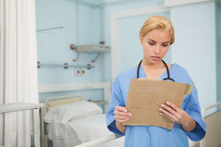 keep watch over: Nurse looking at a folder in hospital ward