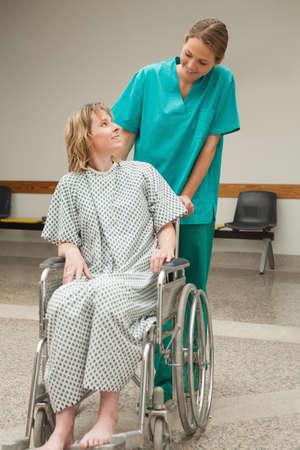 wheeling: Nurse wheeling a female patient sitting on a wheelchair in a corridor
