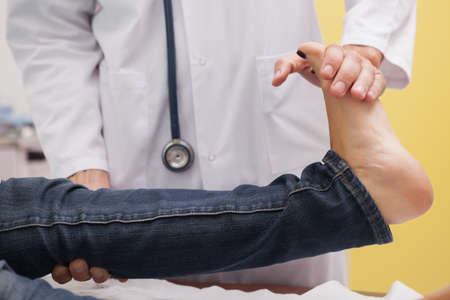 tendons: Doctor auscultating a patient ankle in examination room LANG_EVOIMAGES