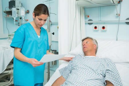 keep watch over: Nurse talking to a patient lying on a bed while holding a paper in a hospital