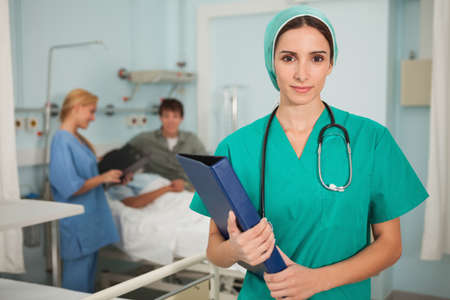 keep watch over: Nurse looking at camera while holding a binder in hospital ward LANG_EVOIMAGES