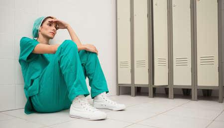 locker room: Tired nurse sitting on the floor in locker room