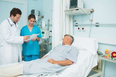 keep watch over: Male doctor and nurse looking at a paper with a patient in a hospital LANG_EVOIMAGES