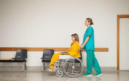 paraplegic: Enfermera empujando la silla de ruedas de un paciente en un pasillo