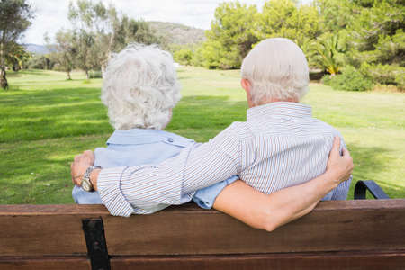 adult 80s: Loving elderly couple on a park bench with their arms around each other LANG_EVOIMAGES