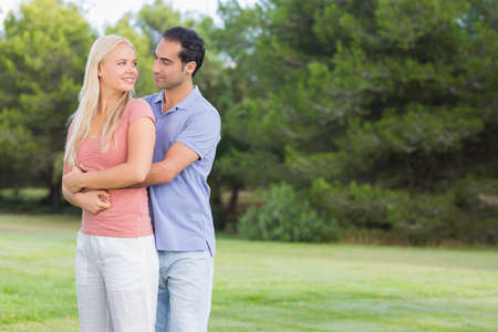 affectionate: Loving couple standing in the park LANG_EVOIMAGES