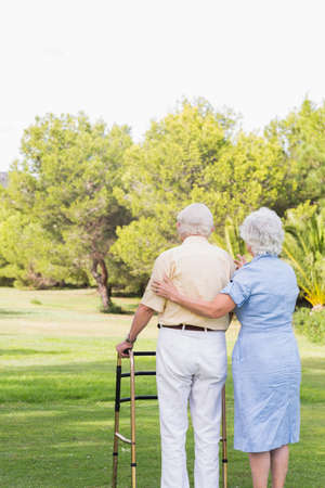 80s adult: Elderly couple standing in park with man using a zimmer frame