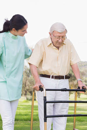 convalescence: Elderly man walking with zimmer frame in the park with his nurse