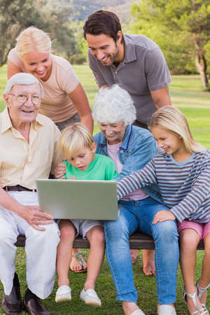 family: Happy multigeneration family in the park using laptop with some sitting on park bench