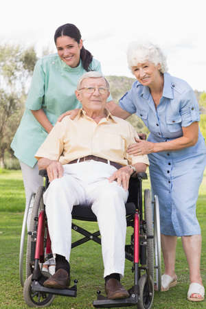 80s adult: Man in wheelchair with his nurse and partner in the park LANG_EVOIMAGES