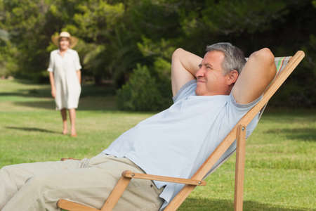 lawn chair: Man relaxing in deck chair with his partner approaching on the lawn
