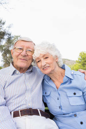 80s adult: Portrait of happy elderly couple sitting in the park on a bench