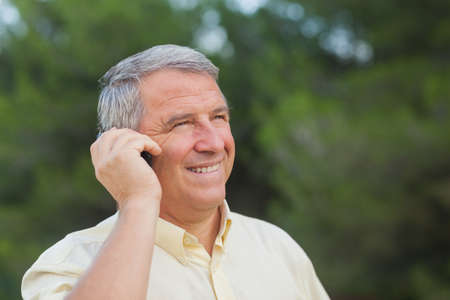 grey haired: Grey haired man using his mobile outdoors in the countryside