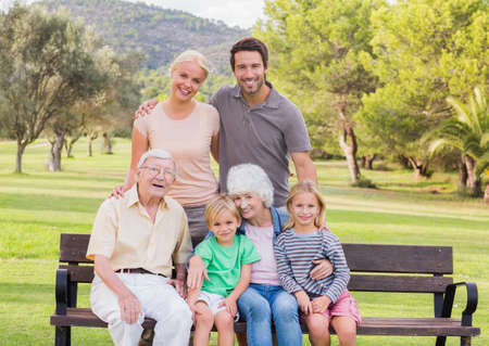 adult 80s: Portrait of multigeneration family in the park smiling with some sitting on park bench LANG_EVOIMAGES