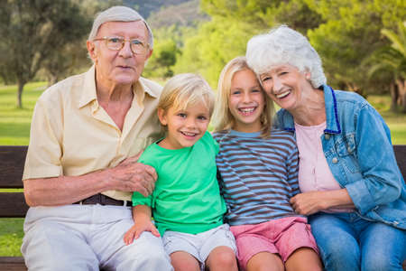80s adult: Portrait of smiling grandchildren with their grandparents sitting on park bench