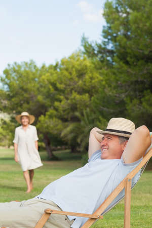 lawn chair: Man in straw hat relaxing in deck chair with his partner approaching on the lawn