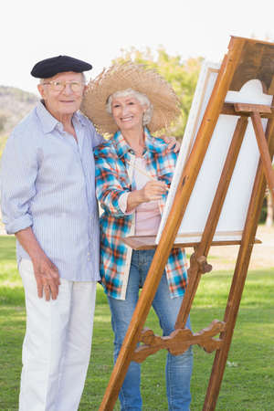 80s adult: Portrait of elderly couple painting in the park and smiling