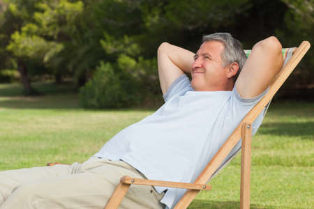 grey haired: Grey haired man relaxing in deck chair