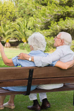80s adult: Elderly woman pointing something out to partner in the park sitting on a park bench