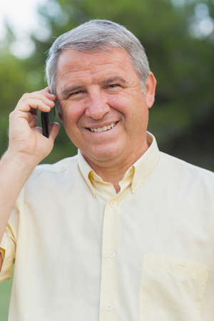 grey haired: Smiling grey haired man on the phone outdoors in the countryside